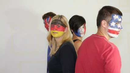 People with flags painted on faces dancing and smiling.
