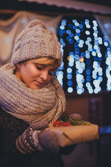 Woman with christmas present in hands near christmas lights