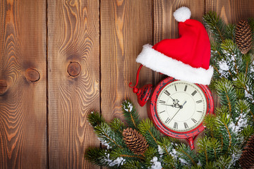Christmas wooden background with clock and snow fir tree