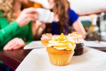 Frauen essen Muffins beim Kaffee trinken