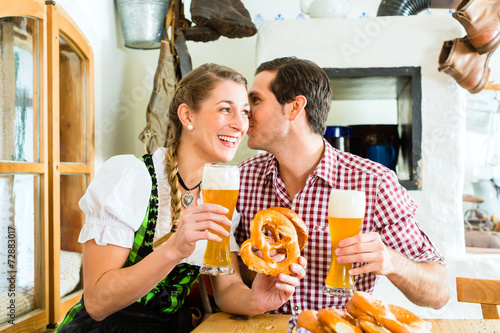 canvas print picture Paar trinkt Weißbier im bayrischen Restaurant