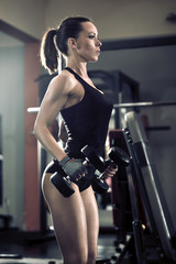 Sporty attractive woman in the gym with exercise equipment