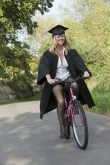 Mature student wearing cap and gown riding a cycle