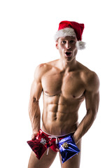 Muscular young man in Santa Claus hat with 2 Christmas gifts