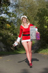 Woman in Santa outfit carrying presents