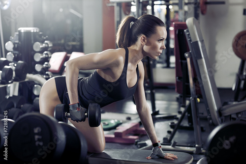 Foto op Plexiglas Fitness Fitness young sexy girl in the gym doing exercises with dumbbell