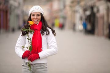 Beautiful young woman holding a single rose
