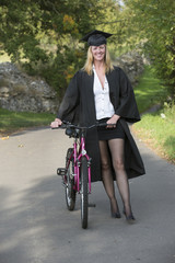 Mature student wearing cap and gown walking with a cycle