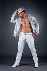 Bearded striptease dancer posing in shiny suit