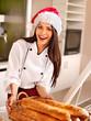 Female chef in Santa hat  holding  food.