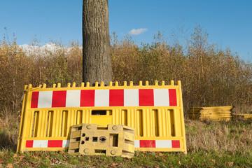 Gelbe Absperrbaken lehnen an einem Baumstamm
