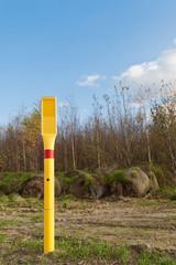 Ein gelber Pfahl aus Kunststoff steht in der Landschaft