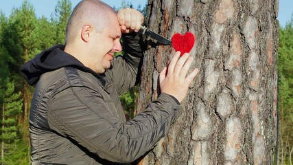 Sorrowful man holding knife and fabric heart near the tree