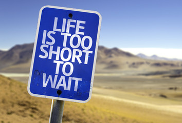 Life is Too Short To Wait sign with a desert background