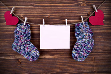 Baby Socks on a Line with Hearts and an Banner with Copy Space