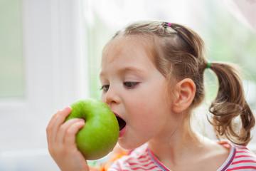 little cute girl biting apple