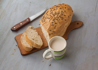 Loaf of rye bread sunflower seeds on a cutting board and cup of