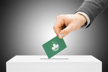 Voting concept - Male inserting flag into ballot box - Macau