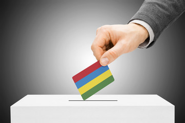 Male inserting flag into ballot box - Mauritius