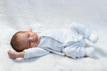 newborn baby sleeping on white fur in  sunlight