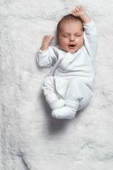 infant yawning stretches on  white fur