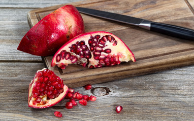 juicy ripe pomegranates with knife on vintage wood server