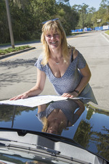 Female driver reading map on bonnet of a car