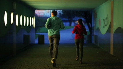 Couple jogging through the tunnel in the city in the evening