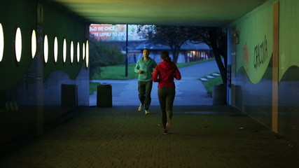 People jogging through the tunnel in the city in the evening