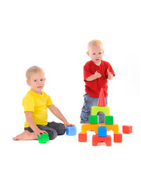 two brothers build toy building of colored cubes