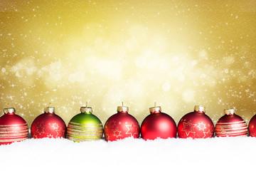 Weihnachtskugeln im Schnee vor festlichem Hintergrund
