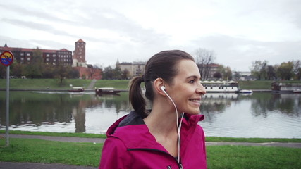 Portrait of young happy female jogger in the city