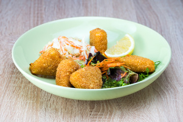 Tasty fried gouda cheese with fresh salad