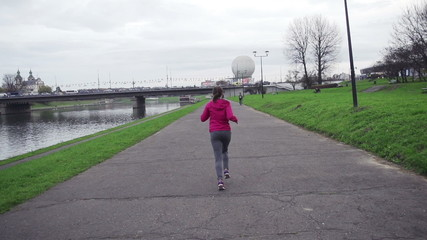 Woman jogging by the river in the city