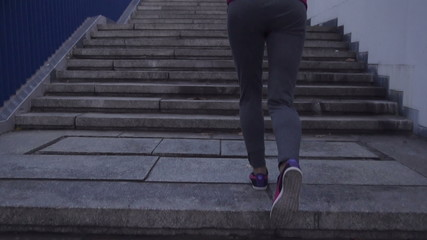 Woman jogging up the stairs in city, super slow motion, 240fps