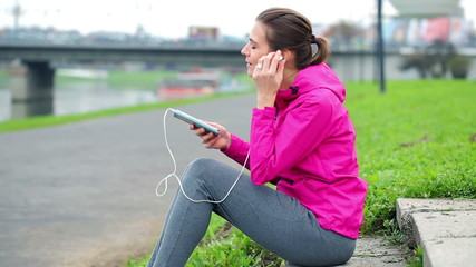 Female jogger resting and listen to the music in the city