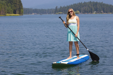 Beautiful woman paddleboarding on scenic lake