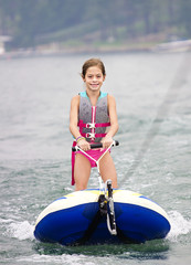Young Girl riding a ski tube behind a boat