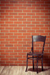 wooden chair before brick wall