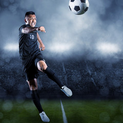 Soccer player kicking ball in a large stadium