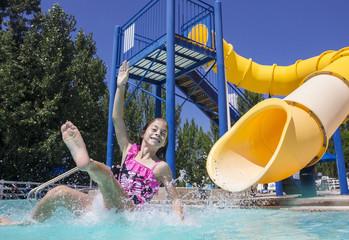 Summertime fun at the water park girl splashing on the slide