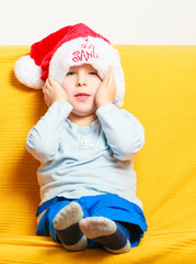 Happy childhood. Boy child kid in santa hat sitting on sofa