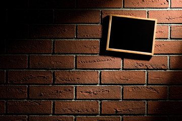blank blackboard hanging on brick wall