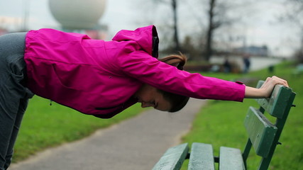 Young sporty woman stretching by the bench in city park