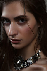 Close-up fashion portrait of horsewoman with big eyes and pendan