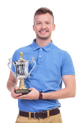 casual young man with trophy in hands