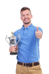 casual young man with trophy shows thumb up