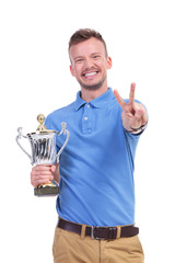 casual young man with trophy shows victory sign