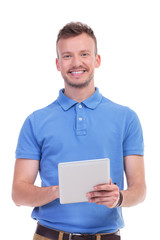 casual young man smiles while holding tablet