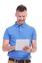 happy casual young man with his tablet